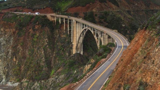 vídeos de stock e filmes b-roll de aerial shot of bixby creek bridge flying behind ridge - big sur