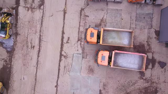 antenn skott av bulldozer och last bilar i utanför lager. drone - construction workwear floor bildbanksvideor och videomaterial från bakom kulisserna