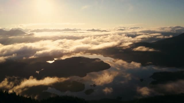 Aerial shot of calm sunrise over clouds and bay with islands video