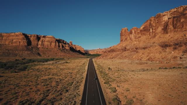 vídeos de stock, filmes e b-roll de aerial shot de carro dirigindo direto americano estrada rodovia entre o cume de montanha rochosa atmosférica desfiladeiro do deserto. - veículo terrestre