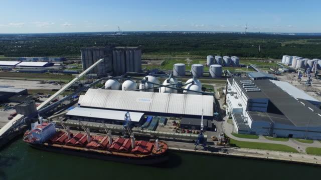 vídeos de stock, filmes e b-roll de foto aérea de porto de cargas com guindastes, silos e navios. - países bálticos