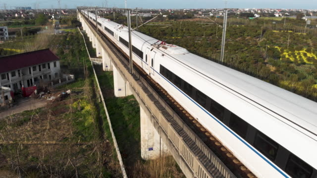 Aerial shot of Chinese high speed rail moving past on raised platform.
