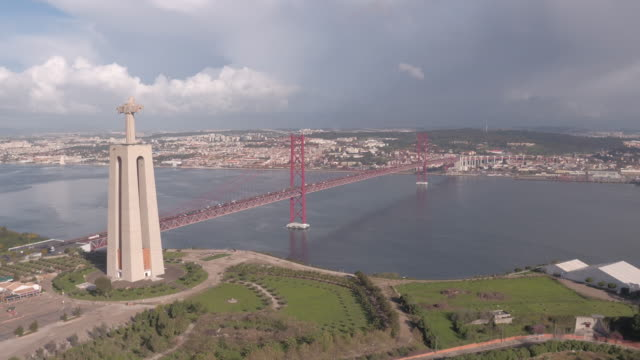 Aerial shot of Christ the King and 25 de Abril Bridge Aerial shot of Christ the King monument and 25 de Abril Bridge, Lisbon. ponte 25 de abril stock videos & royalty-free footage