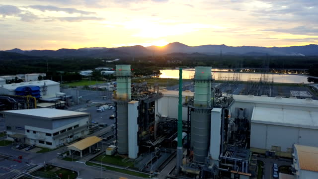 aerial shot of combine cycle powerplant and cooling tower during sunset - anidride carbonica video stock e b–roll