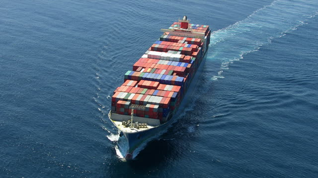 Aerial shot of container ship in ocean HD 1080p: Aerial shot of container ship in ocean.  Shot with a Cineflex gyro-stabilized camera system.  commercial dock stock videos & royalty-free footage