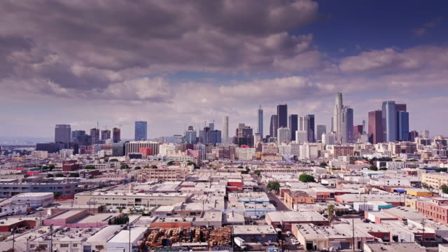 Aerial Shot of DTLA Drone shot flying over warehouses and lofts, towards the skyscrapers of Downtown Los Angeles. warehouse aerial stock videos & royalty-free footage