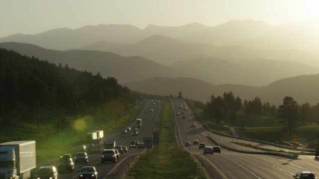aerial shot of east and westbound highway traffic along interstate-70 in the rocky mountains of colorado at sunset - колорадо стоковые видео и кадры b-roll