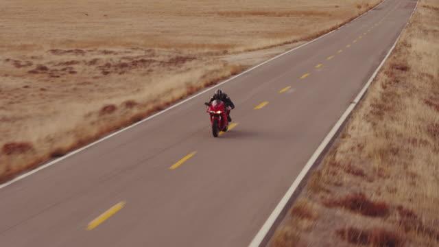vidéos et rushes de aerial shot d'extrême homme course moto sur route droite au coucher du soleil - vue en contre plongée