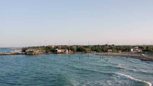 güneşli günde balıkçı kulübelerinin havadan çekilmiş fotoğrafı - ravenna stok videoları ve detay görüntü çekimi