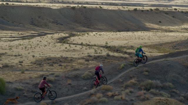 aerial shot of four mountain bikers riding along a curved ridge on 18 road in fruita, colorado - percorso per bicicletta video stock e b–roll