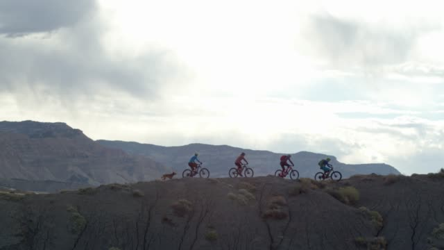aerial shot of four mountain bikers riding along a ridge on 18 road in fruita, colorado - колорадо стоковые видео и кадры b-roll