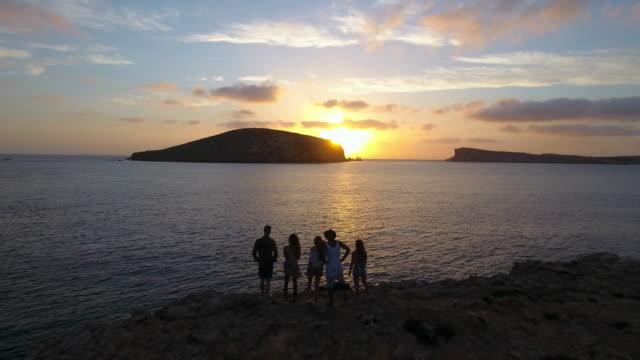 aerial shot of friends on cliffs watching sun set over sea - ibiza filmów i materiałów b-roll