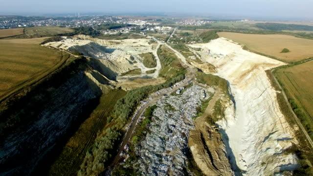 Aerial shot of garbage dump between agricultural fields video