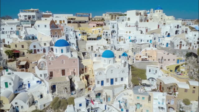 aerial shot of greek santorini island with blue dome churches in oia. - grekisk kultur bildbanksvideor och videomaterial från bakom kulisserna