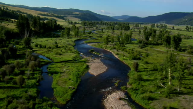 aerial shot of green valley river and ranch in the distance - ranch video stock e b–roll