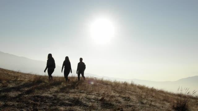 vídeos de stock e filmes b-roll de aerial shot of hikers walking along a mountain ridge - suíça