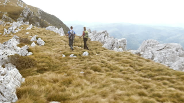 Aerial shot of hiking couple walking the mountain ridge video