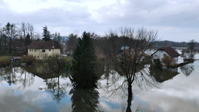 Aerial shot of houses in flooded area Aerial tilt up shot showing houses on a flooded marsh with a large flooded area in the background due to heavy rain. slovenia stock videos & royalty-free footage