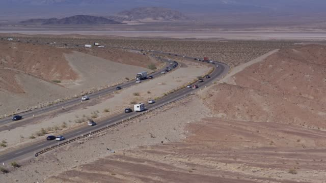 Aerial Shot of I-15 Curving Through the Mojave Desert Drone shot of Interstate 15, a divided highway crossing the Mojave Desert near the town of Zzyzx. mojave desert stock videos & royalty-free footage