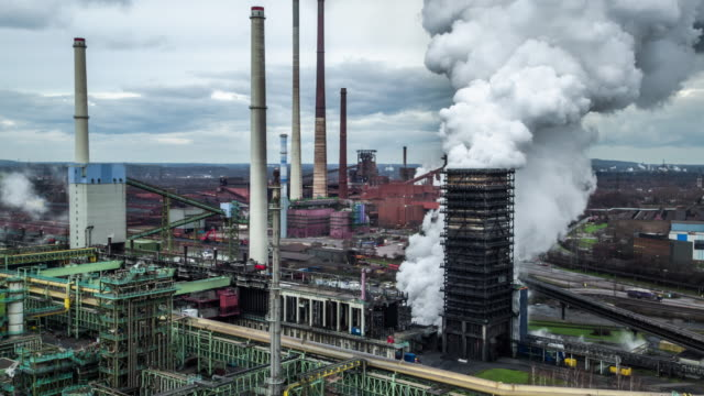 Aerial shot of Industry - Coking Plant Aerial shot of steam rising up from a cooling tower at Schwelgern steel plant in North Rhine Westphalia, Germany. steel mill stock videos & royalty-free footage