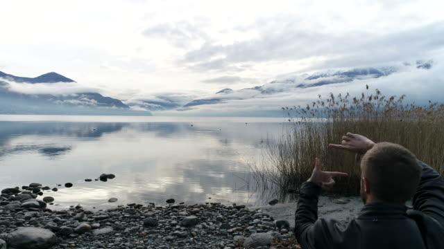vídeos de stock e filmes b-roll de aerial shot of man making natural finger frame by the lake - lago maggiore