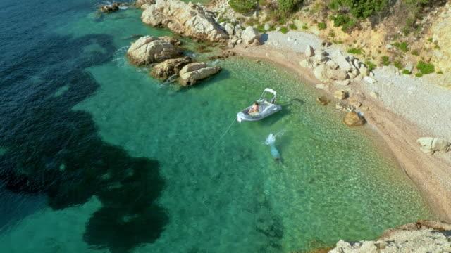 aerial shot of man swimming in bay near his boat - хорватия стоковые видео и кадры b-roll