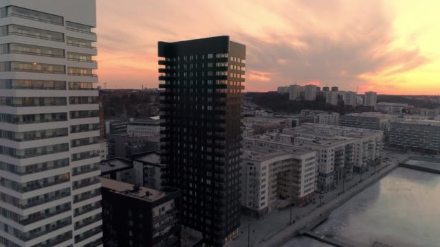 Aerial shot of modern office buildings at dusk in Stockholm, Sweden. Drone shot view of contemporary residential district, next to frozen ice bay Aerial shot of modern office buildings at dusk in Stockholm, Sweden. Drone shot view of contemporary residential district, next to frozen ice bay stockholm stock videos & royalty-free footage