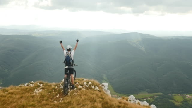 Aerial shot of mountain biker on top with hands raised video