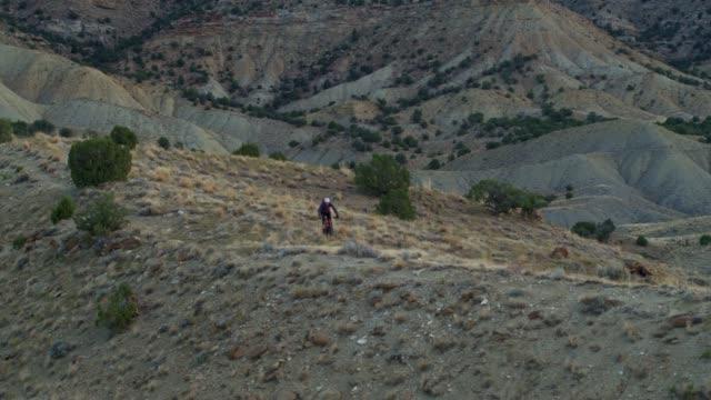 aerial shot of mountain biker riding along a ridge on 18 road in fruita, colorado - bike tire tracks video stock e b–roll