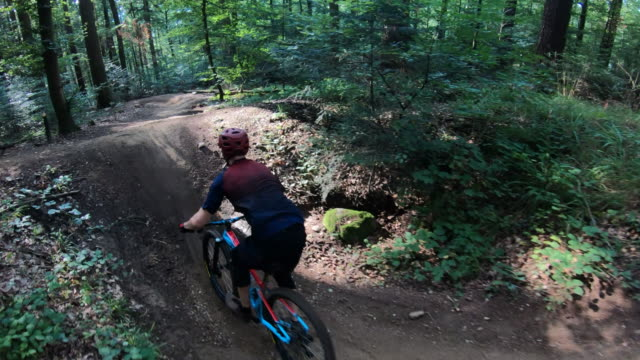 aerial shot of mountain bikers descending a mountain trail through the forest - andare in mountain bike video stock e b–roll