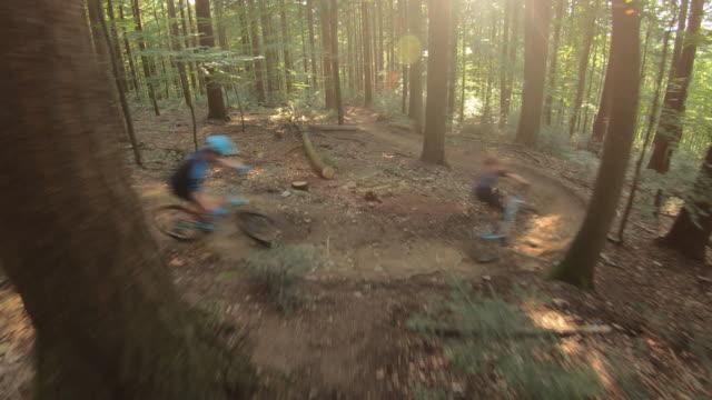 stockvideo's en b-roll-footage met luchtfoto van mountainbikers die een bergpad door het bos afdalen - minder dan 10 seconden
