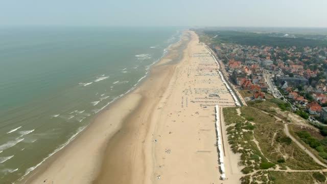 riprese aeree del mare di nothern e della spiaggia sabbiosa vicino alla città - belgio video stock e b–roll