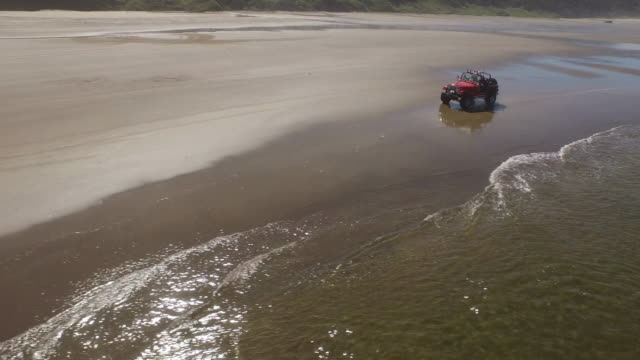 Aerial shot of off road vehicle driving on beach video