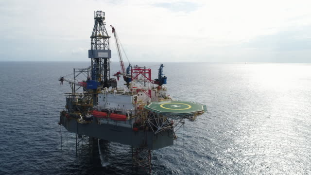 Aerial shot of off shore oil platforms working close up day time