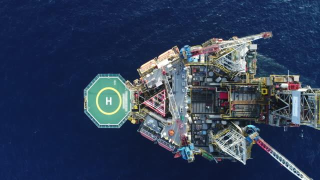 vídeos de stock, filmes e b-roll de tiro aéreo de plataformas de petróleo off shore trabalhando de perto o tempo do dia - gasolina