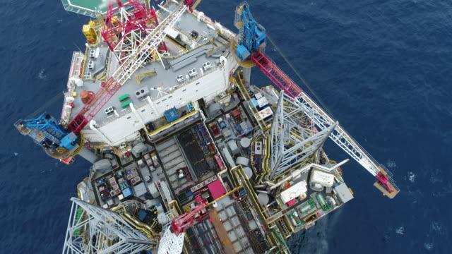 vídeos de stock, filmes e b-roll de tiro aéreo de plataformas de petróleo off shore trabalhando de perto o vídeo de estoque do dia - equipamento
