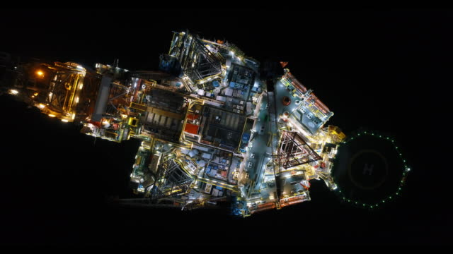 Aerial shot of off shore oil platforms working close up night time