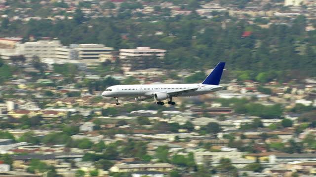 Aerial shot of passenger jet flying over city video