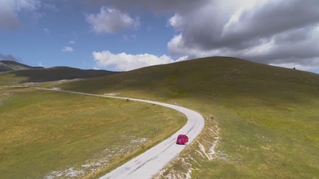 イタリアの豊満山道で赤い suv 車の空中ショットは。 - 陸の乗り物点の映像素材/bロール