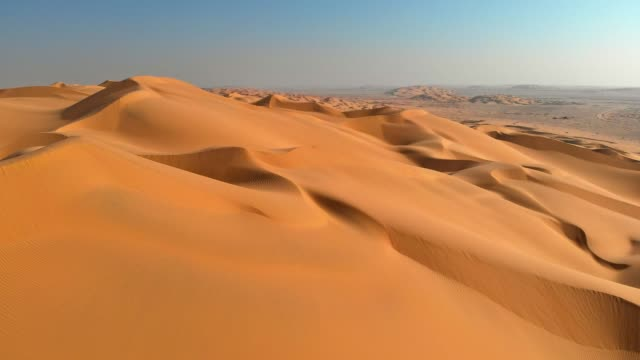 aerial shot of sand dunes in desert. flying over endless yellow sand dunes at sunset - paesi del golfo video stock e b–roll