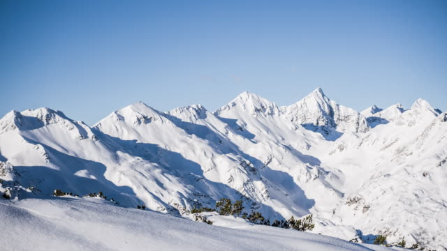 Aerial shot of snowcapped mountains on a sunny winter day Aerial shot of idyllic snowcapped mountains on a sunny winter day on a clear sky background, as seen from a ski lift snowcapped mountain stock videos & royalty-free footage