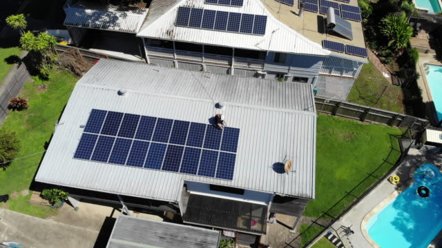 vídeos de stock e filmes b-roll de aerial shot of solar panel technician with drill installing solar panels on roof - energia solar
