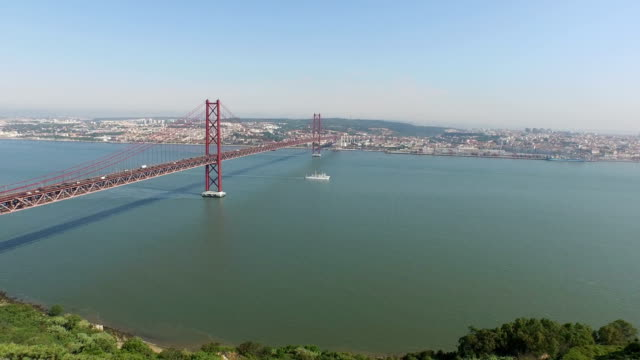 Aerial shot of the 25th of April bridge and Tagus River Aerial shot of the 25th of April bridge and Tagus River, in Lisbon, Portugal. ponte 25 de abril stock videos & royalty-free footage