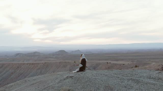 aerial shot av kameran kretsande jesus kristus knästående och be med palms upp på en öken sluttning med ett tält och berg bakom honom vid sol uppgång/solnedgång - endast en man i 30 årsåldern bildbanksvideor och videomaterial från bakom kulisserna