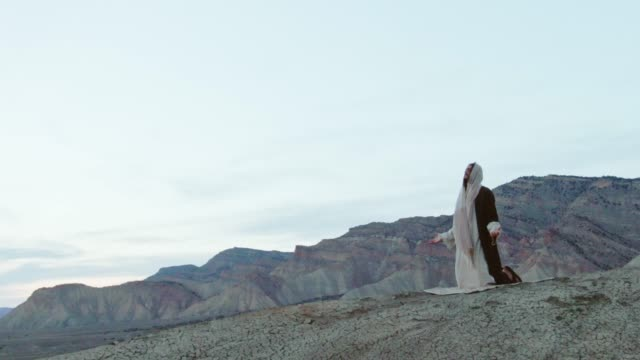 vídeos de stock e filmes b-roll de aerial shot of the camera circling jesus christ kneeling and praying with arms out on a desert hillside with a tent and mountains behind him at sunrise/sunset - cristo redentor