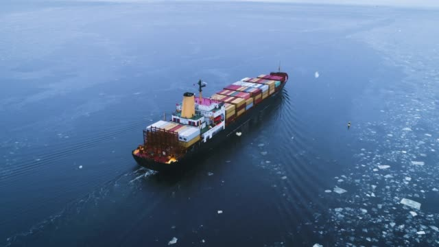 Aerial Shot of the Cargo Ship Moving Through the Sea. In the Background Winter Landscape.