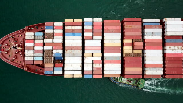 vídeos de stock e filmes b-roll de aerial shot of the cargo ship moving through the sea. - navio