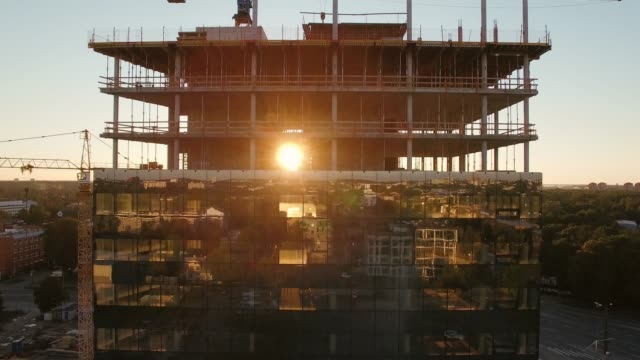 aerial shot of the skyscraper building in the process of construction. in the background working crane, forest, sea and sunset. - industria edile video stock e b–roll