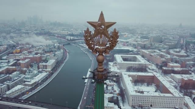 antenn skott av stjärnan i stalins byggnad - symbol för kommunismen. i bakgrunden moskva floden, moscow city och snö på hus. - kreml bildbanksvideor och videomaterial från bakom kulisserna