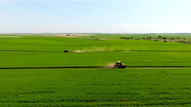 vidéos et rushes de vue aérienne de champ de tracteur pulvérisation - californie du sud